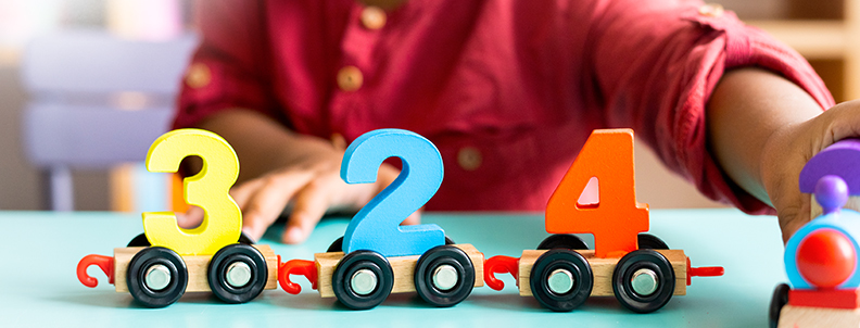 young children playing with numbers on wheels