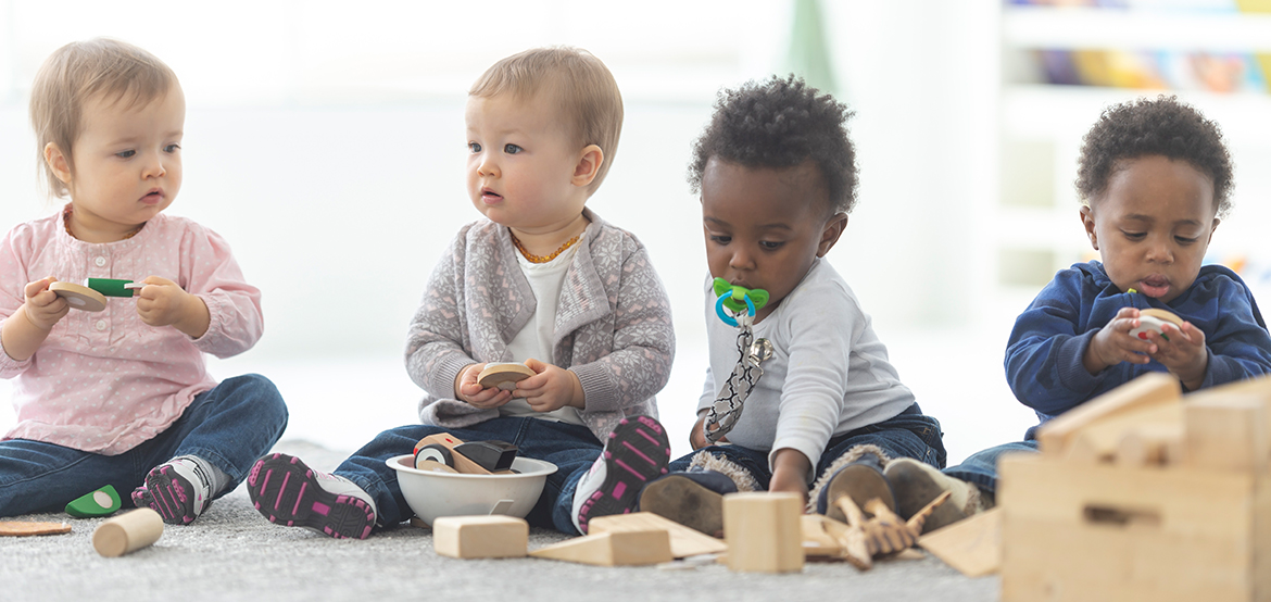young babies playing with blocks and toys